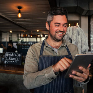 restaurant manager checking his iPad - commercial solocitors at mullins treacy solicitors