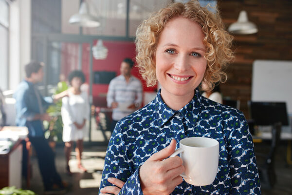 lady standing with a cup in an office - mullins treacy solicitors