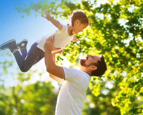 picture of father and child with green trees and blue skies by Mullins Treacy Solicitors Waterford